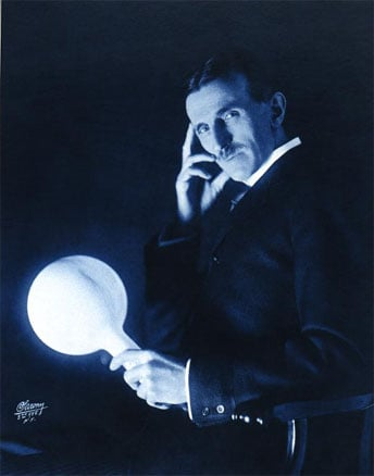 Nikola Tesla with a gas-filled light bulb illuminated without wires.