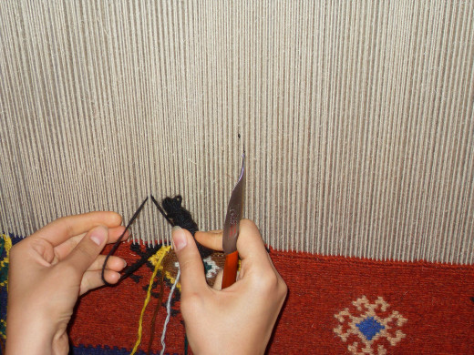 Hand weaving an Iranian rug.