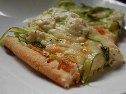 A close-up of a slice of pizza with shredded asparagus and cheese on top.