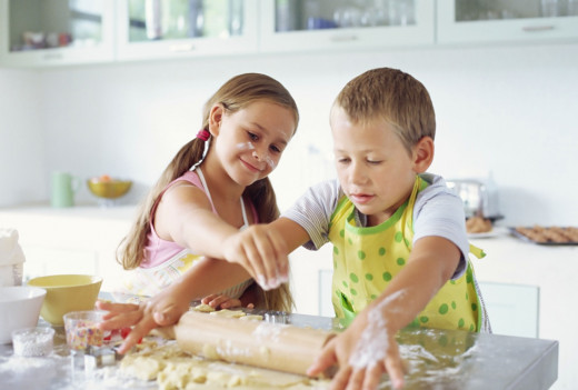 Two children, a boy and girl, working together in the kitchen to bake a pizza.