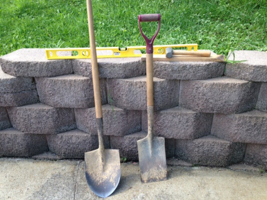 Rounded shovel, squared shovel, level, mallet and scrap wood.