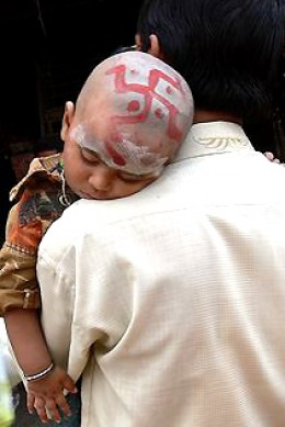 Father and sleepy child; a symbol of good luck is daubed on the child's head