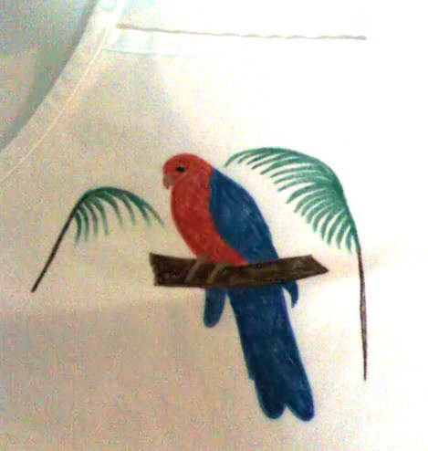 Painting of a parrot on a cloth apron. The outline design of the parrot was there first. The branches were added free hand.