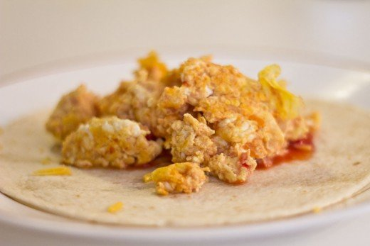 A breakfast wrap with scrambled eggs and salsa.