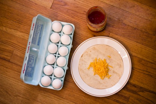 Eggs, salsa, shredded cheddar cheese, and a flour tortilla.