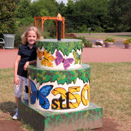 Ella is standing by one of the many birthday cakes that are found throughout the area in honor of the 250th birthday of St. Louis.