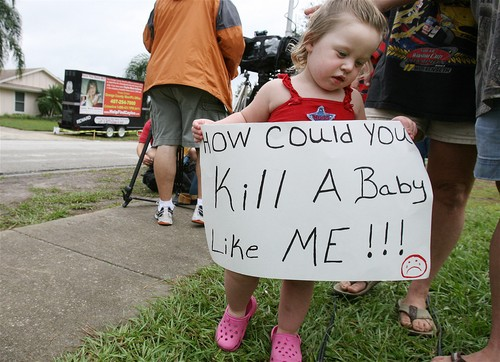 Child holds a sign in front of Anthony home