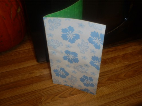 """Glue scrap booking paper to the front of the card to cover up the hole made by the """"pop-up"""".  Sometimes I draw a design for the front, or I use the computer to make one.  Lately I have discovered using a scrapbooking page works very well."""