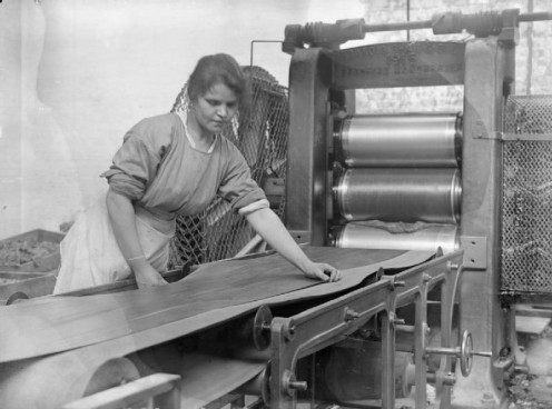 A female worker operates a calendering machine in the rubber factory of Charles Macintosh and Sons Ltd, Manchester, in September 1918.