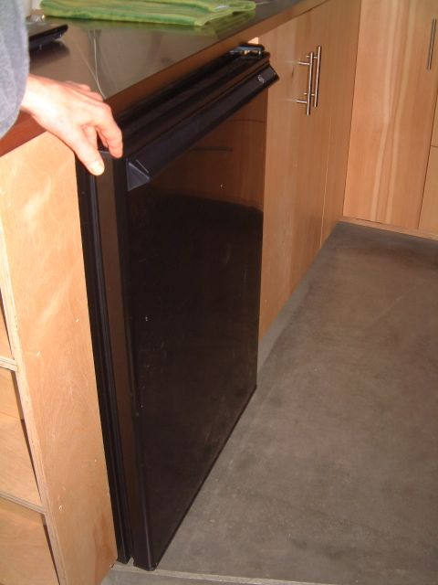 There was a refrigerator below the counter.  There was talk of how some of the eating bar could be swapped out to install a teeny washer/dryer.