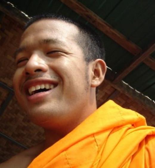 A monk smiling, by Tevaprapas Makklay, public domain