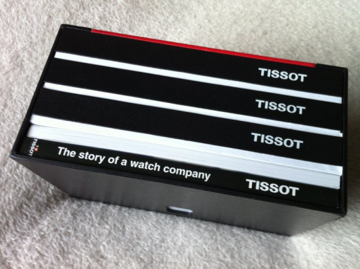The presentation box includes a book on the history of Tissot watches