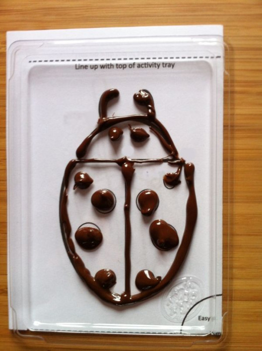 Use the dark choccie to outline the shape. My first attempt wasn't brilliant because I cut the wrong corner off the pack.