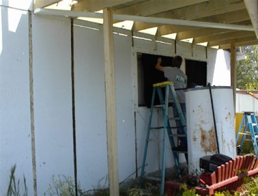 In this picture he's covering the window openings for the kitchen and bedroom windows until he can put them back in.