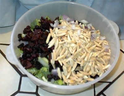 Put the dry ingredients -- chopped broccoli, dried fruits, chopped red onions, and slivered almonds into a bowl.