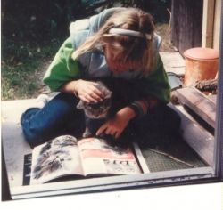 Sarah showing Mr. Cat a book about cats.