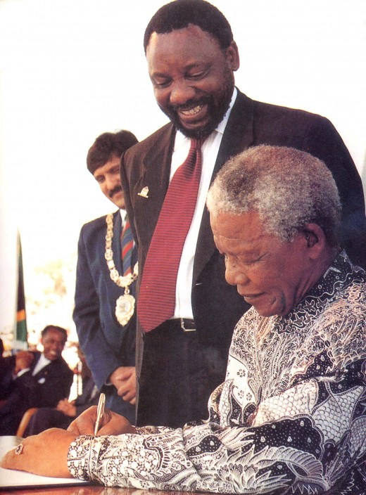 Former president Nelson Mandela signs the South African Consititution into law in 1996, watched by Mr Cyril Ramaphosa