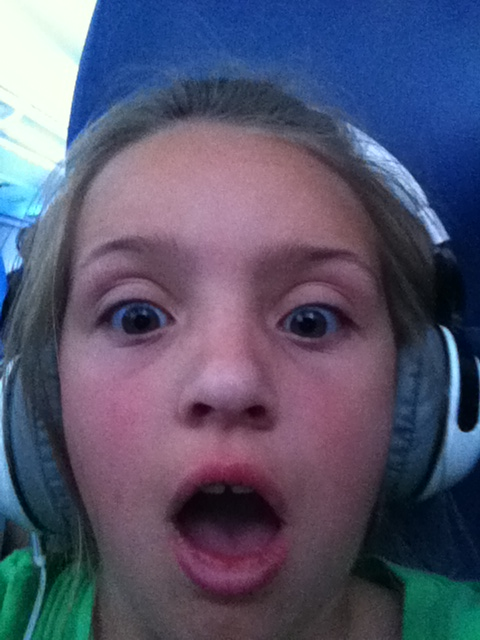 A picture of my daughter being silly on an airplane wearing her Skullcandy Paul Frank headphones in white.
