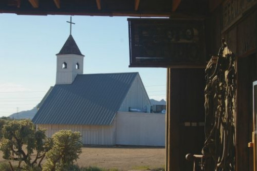 View of the chapel from inside the barn. On the right, faintly seen, are bridles and other leather devices.
