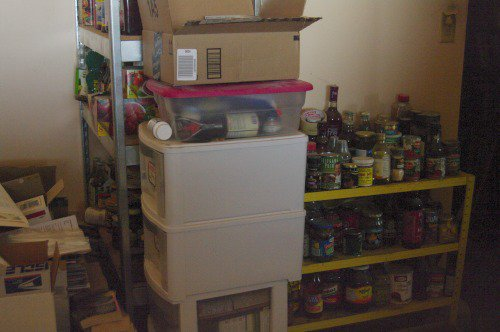 A food storage shelf in the kitchen. It will have to be moved temporarily to make space for moving the couch.