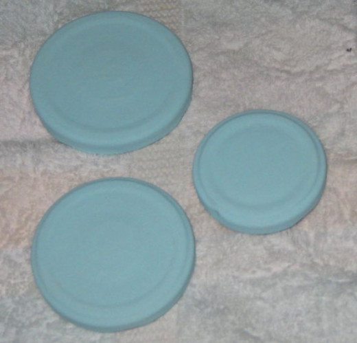 Paint the jar lids with acrylic craft paint. Set them on a plastic or cloth surface (not paper) so they won't stick. I usually give the lids two good coats.