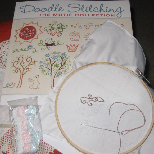 Getting started with beginning embroidery. Shown are the book, embroidery hoop, needle, floss, and handkerchief being stitched.
