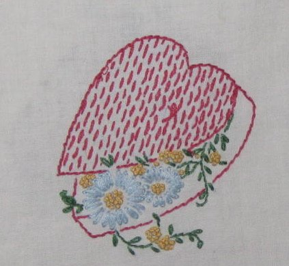 Card suits are embroidered on this vintage tablecloth.