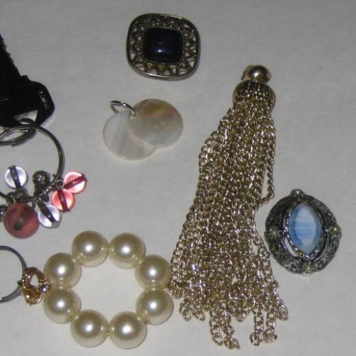 Selection of costume jewelry for making keychains. Look for pieces that have a hole or loop for adding the key ring to.