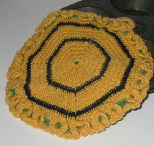 Crocheted potholder with green peeking out under the gold.