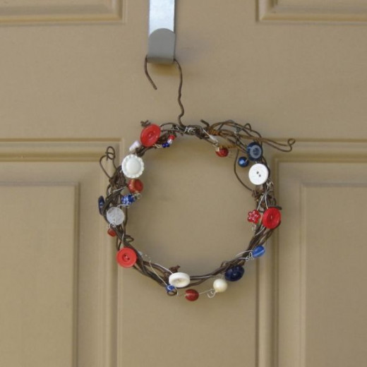Simple wire wreath adorned with red, white, and blue buttons and beads.