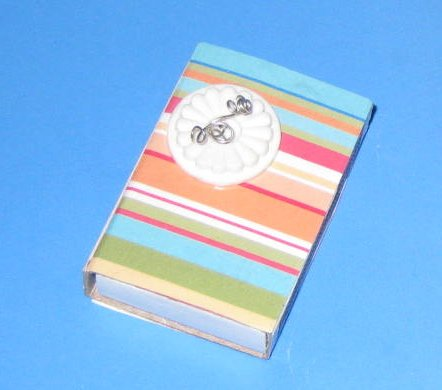 Make covered matchboxes with scrapbook paper, Mod Podge, a button, and wire.