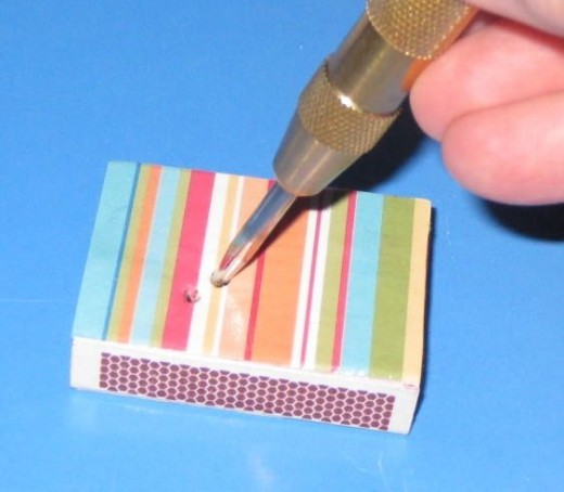 If you want to add beads or buttons to the top of the matchbox, use a hole punch to puncture the box. Be sure to line up the holes with the button holes.