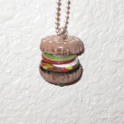 A found object hamburger pendant I made. With junk.
