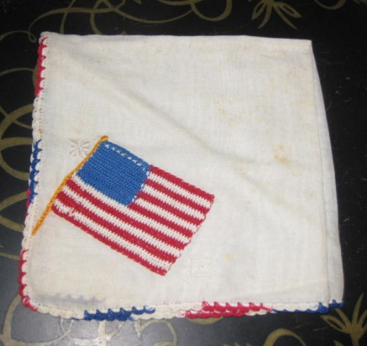 Flag hankie. Flag stitched on white cotton handkerchief with red, white, and blue tatted border.