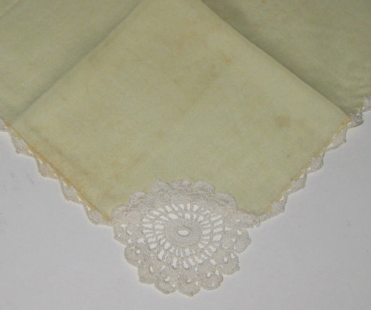 White embroidery on yellow hankie.