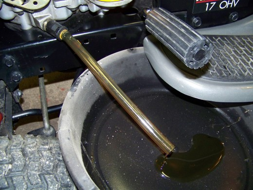 Put an oil pan under the other end of the plastic tube then twist and pull the drain valve.The cold oil will start to drain in the pan slowly.