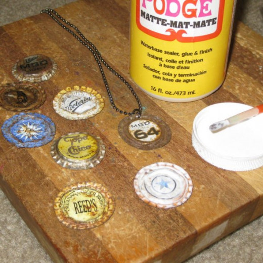 Add a sealant like Mod Podge to the rusty bottle caps to keep the rust from touching the person who will be wearing the pendant.