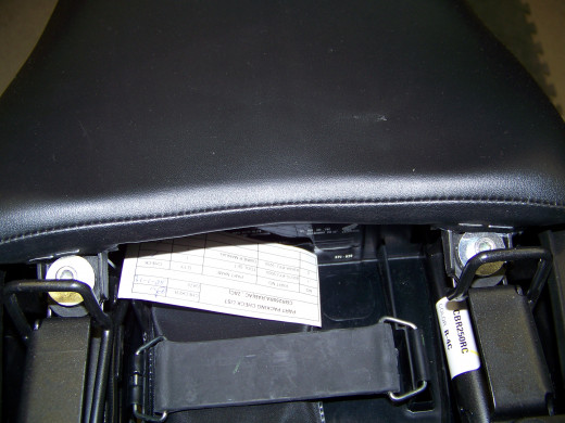 The front seat is held in place in the back by two hex head bolts. Remove then push seat forward and pull up.