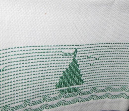 Stitch work depicting a sailboat on vintage kitchen towel.