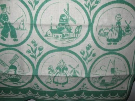VIntage tea towel with Dutch designs:  windmills, Dutch girl, Dutch boy, and more.