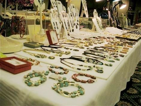 Hand crafted jewelry on display at a craft show.