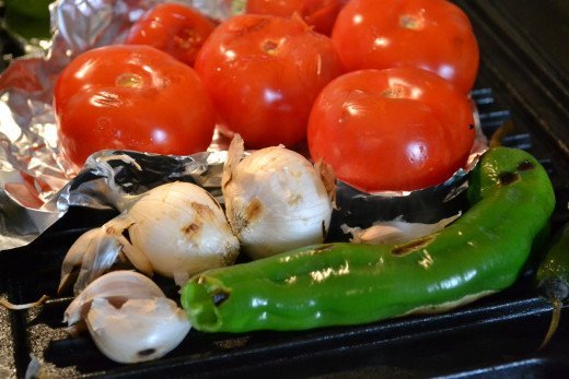 Make roasted vegetable salsa by placing skin-on onions, garlic, peppers and tomatoes on the grill. Place foil under the tomatoes so they don't stick.