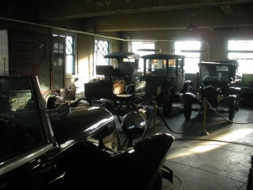 The middle car in the rear row was a 1914 electric-powered vehicle. The seating arrangement was such that the driver was in the back seat, and it was spacious enough that a person could stand up inside. The car to the left in the row is an earlier el