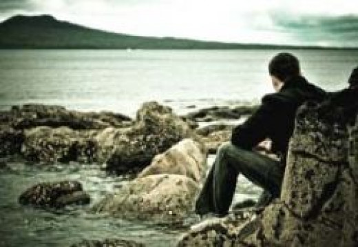 Person sitting, staring out at the ocean