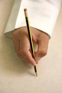 A hand with a pencil about to write on a blank page