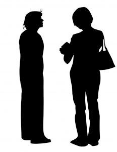 Silhouettes of two friends talking, one standing stiff and the other relaxed and open-looking