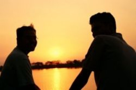 Two friends comfortably talking with each other while watching a sunset