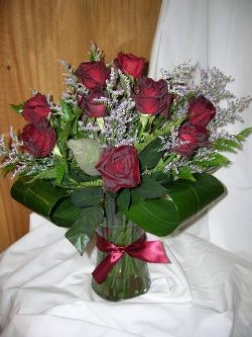 A hand-tied dozen red roses with limonium and premium foliage including aspidistra leaves in a glass vase