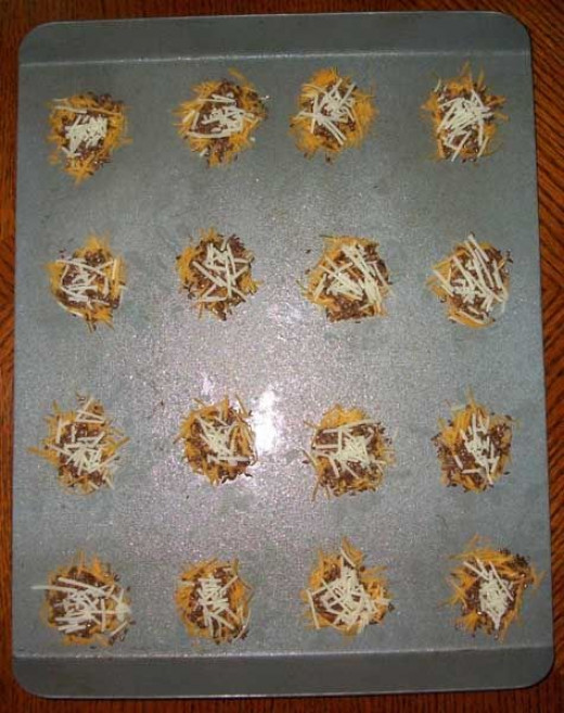 More cheese atop unbaked crackers