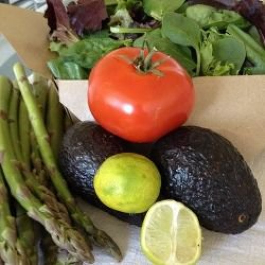 Our picnic salad starts with a box of spring greens from the supermarket salad bar, fresh raw asparagus spears, a garden-ripe tomato and two avocados, which we will drizzle with fresh-squeezed lime juice
